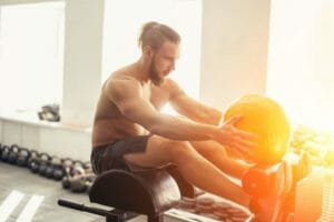 Man on rowing machine with weight ball in gym